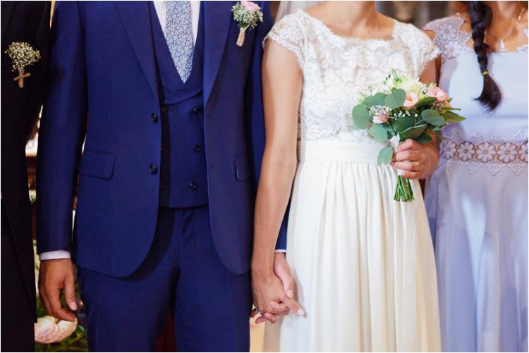 Les mariés se tiennent par les mains à l'église