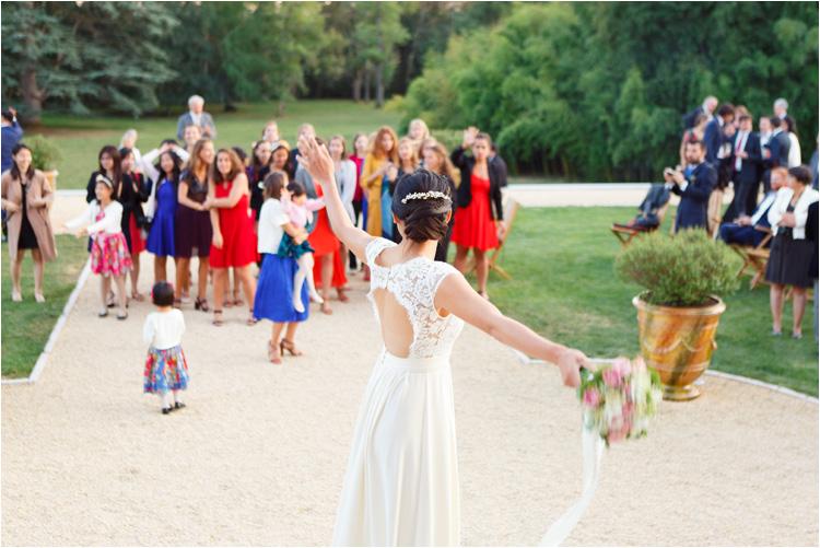 La mariée lance son bouquet aux filles au mariage